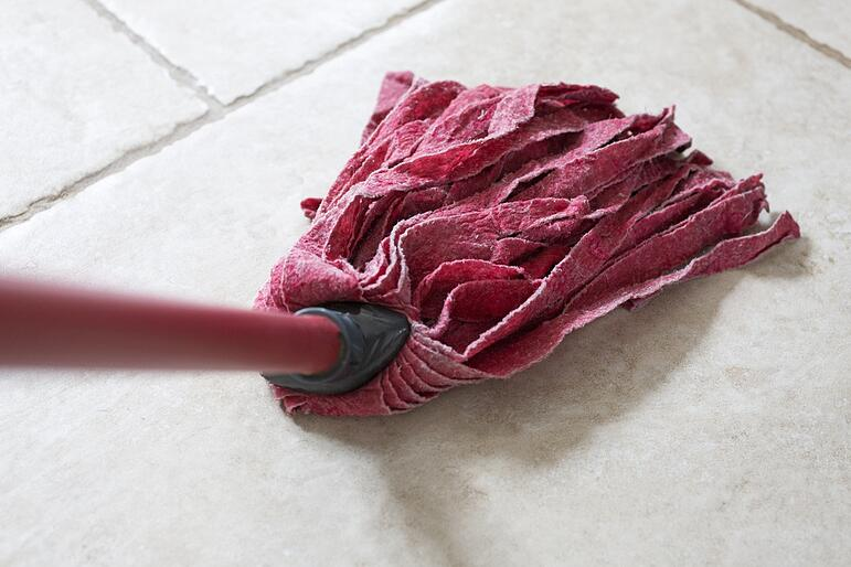 Red kitchen mop being used to clean a floor surface.jpeg