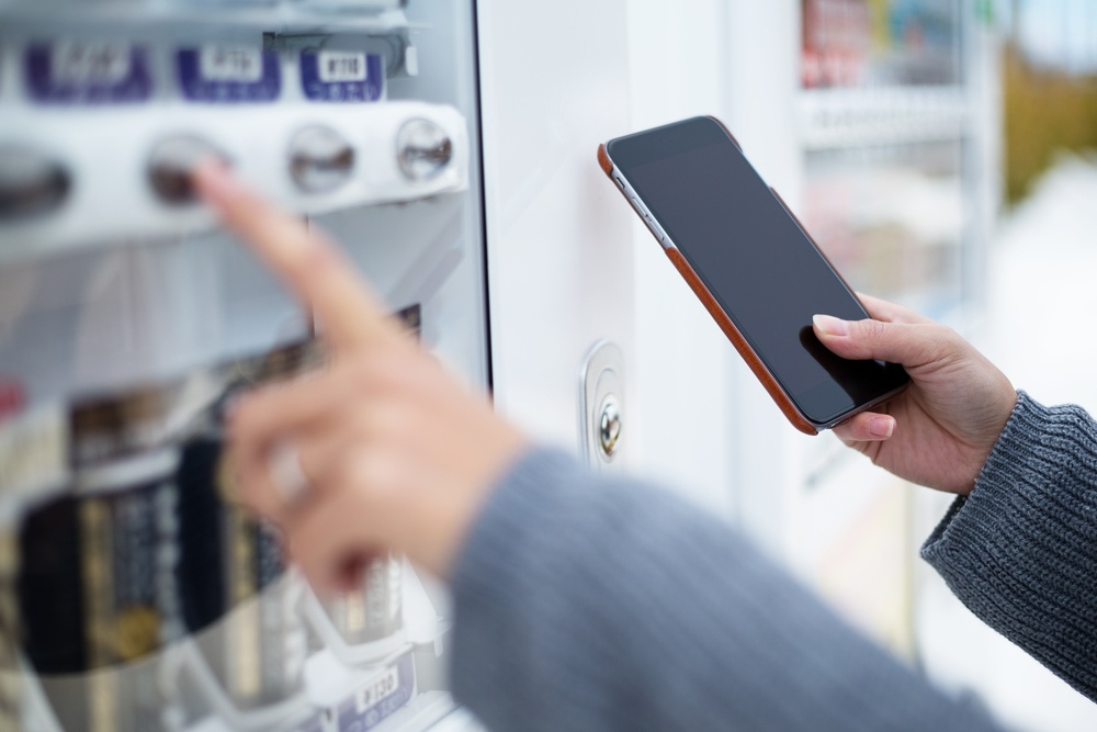 Woman use of soft drink vending system paying by cellphone.jpeg